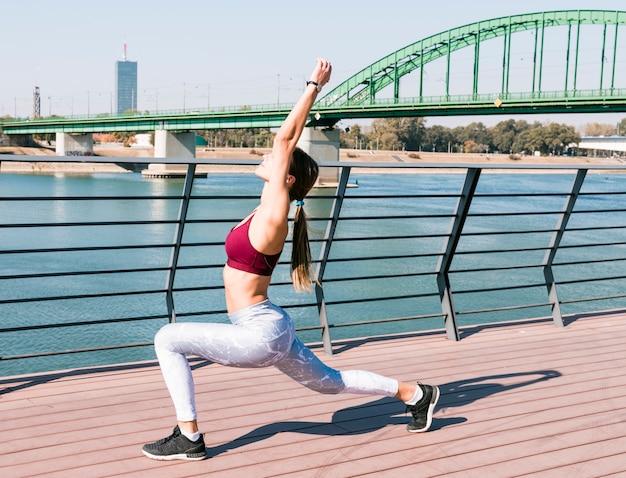 橋の上の運動中に彼女の足と手を伸ばして健康的な若い女性