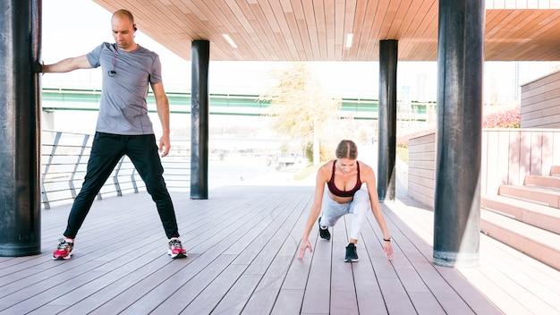 トレーニングの前に公園でストレッチ体操をしているスポーティなカップルの肖像画