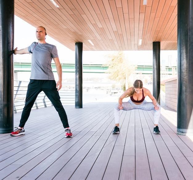 いくつかのストレッチ体操をしている運動選手カップルの肖像画
