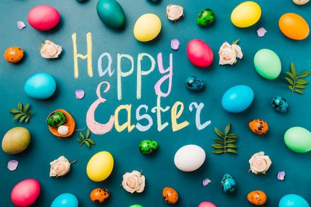 枝、花、着色された卵のセットの近くのハッピーイースターのタイトル