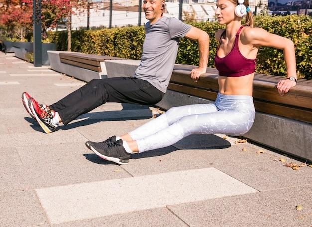 公園でストレッチ運動をしている幸せなカップル