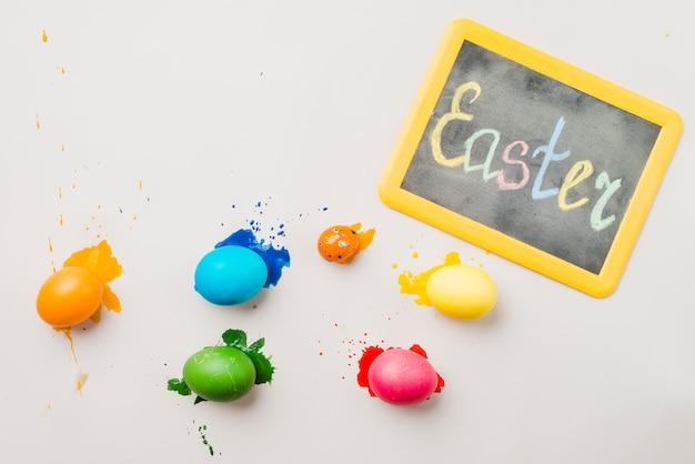 着色された卵のセットの近くのイースターのタイトルと黒板