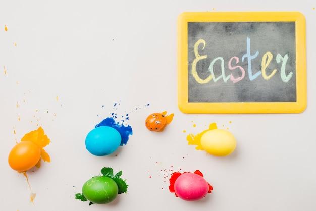 着色された卵のコレクションの近くのイースターのタイトルと黒板