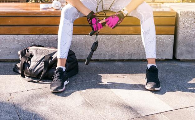 縄跳びを手に持ってベンチに座っているフィットネス若い女性の低いセクション