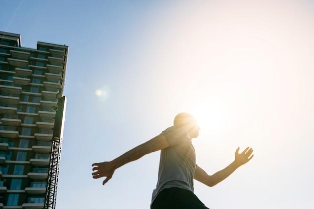 青い空を背景に走っている男性ランナーの上に落ちる日光