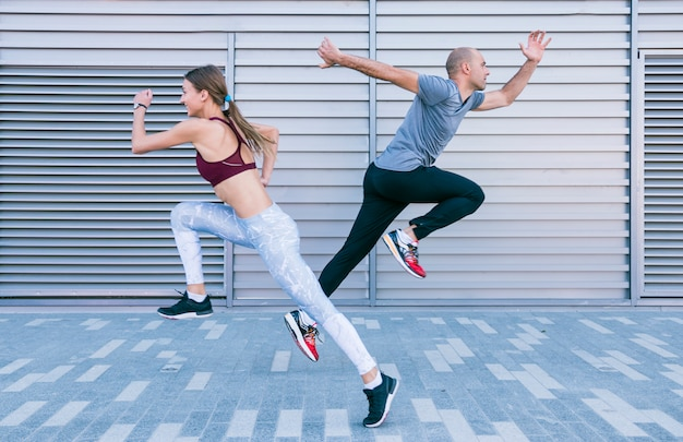 アクティブで陽気な若い男性と女性のアスリートを実行していると空気中のジャンプ
