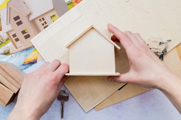 木製のミニチュアの家モデルを持っている手のクローズアップ