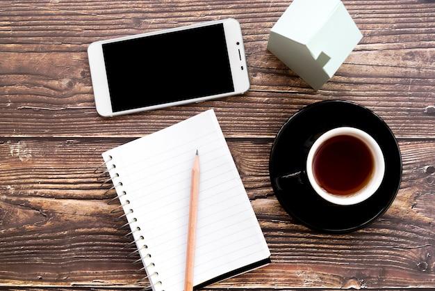 携帯電話;空白のスパイラルノート。鉛筆;木製の机の上のコーヒーカップと家のモデル