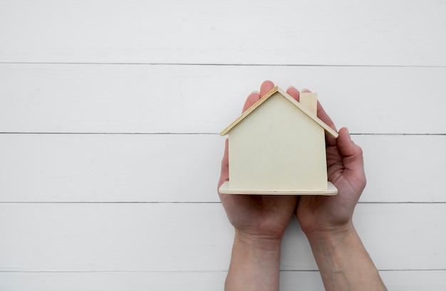 木製の白い背景に対して木製のミニチュアの家モデルを持っている手のクローズアップ