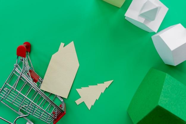 緑色の背景でショッピングトロリーと紙の家の俯瞰