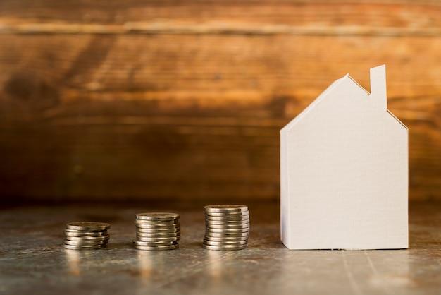 表面の紙の家の近くのコインのスタックを増やす