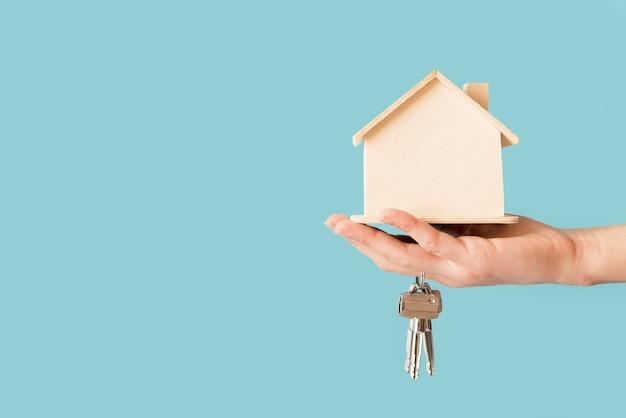 キーと青い背景に対して木造住宅モデルを持っている手のクローズアップ