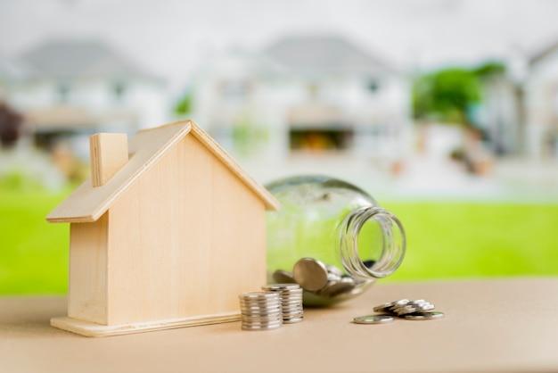 開いたガラス瓶。屋外のテーブルの上の木造住宅モデルの近くのコイン