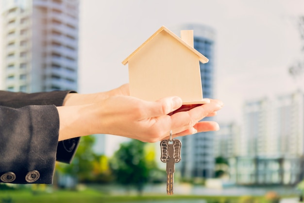 Крупный план женской руки, держащей деревянную модель дома и ключи на фоне затуманенное здания