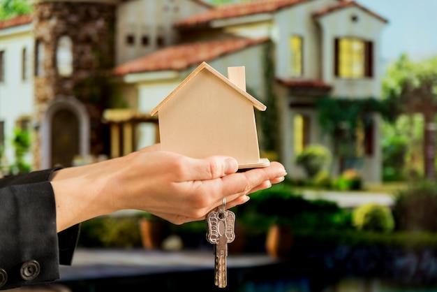 Рука бизнес-леди держа деревянную модель дома и ключи против дома нерезкости