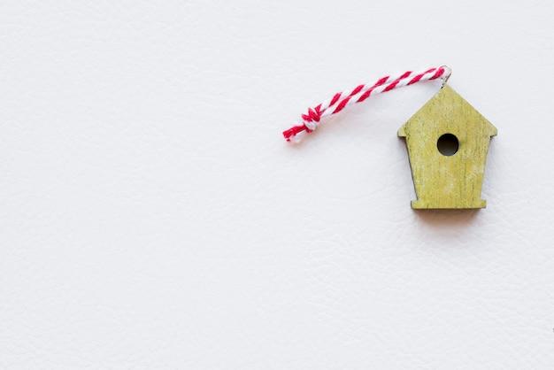 白い背景の上の縞模様のスレッドを持つ小さな黄色の木の鳥の家