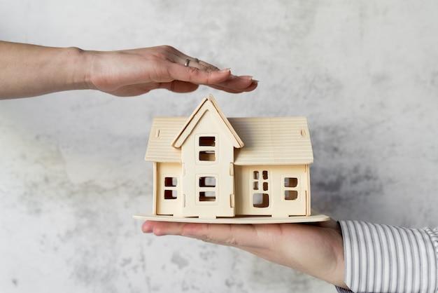 コンクリート背景に対して人による家の保持を保護する女性の手のクローズアップ
