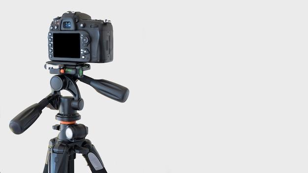白い背景の上の三脚にデジタル一眼レフカメラのクローズアップ