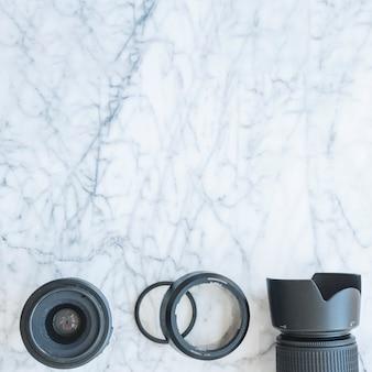 大理石の背景にレンズとエクステンションリング付きデジタル一眼レフカメラの立面図