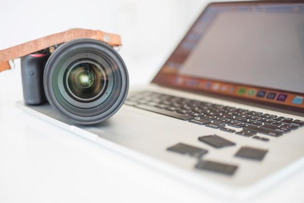 プロの現代的なカメラとラップトップ上のメモリカード