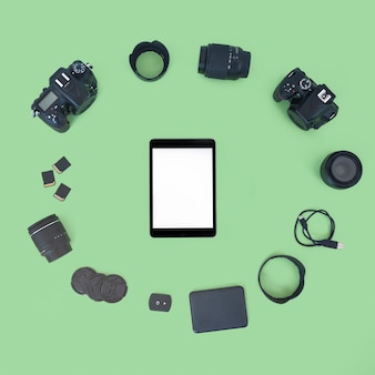 プロのデジタルカメラと緑色の背景上のアクセサリーに囲まれた空白の画面デジタルタブレット