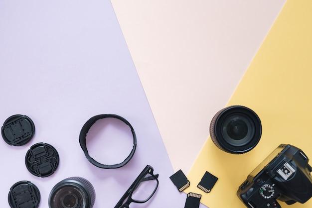 カメラのアクセサリーと色付きの背景上の眼鏡を持つ近代的なデジタル一眼レフカメラ