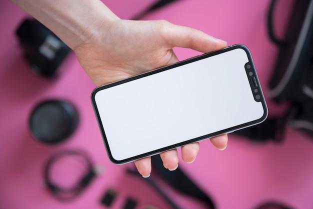 空白の画面を持つ携帯電話を示す人の手のクローズアップ