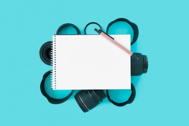 青い背景にカメラアクセサリーの上にペンで空白のスパイラルメモ帳