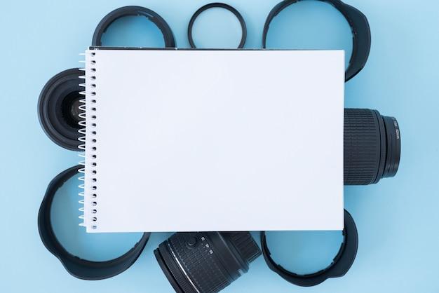 青い背景のカメラアクセサリーの上の空白のスパイラルメモ帳の立面図