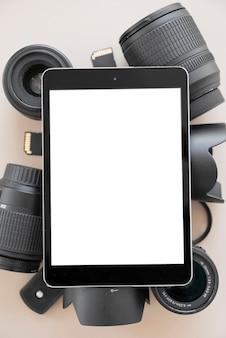 カメラのレンズと色付きの背景上のアクセサリーの上の空白の画面を持つデジタルタブレット