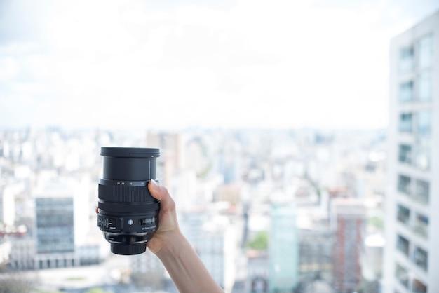 ぼやけている建物の背景の前にカメラのレンズを持っている人の手