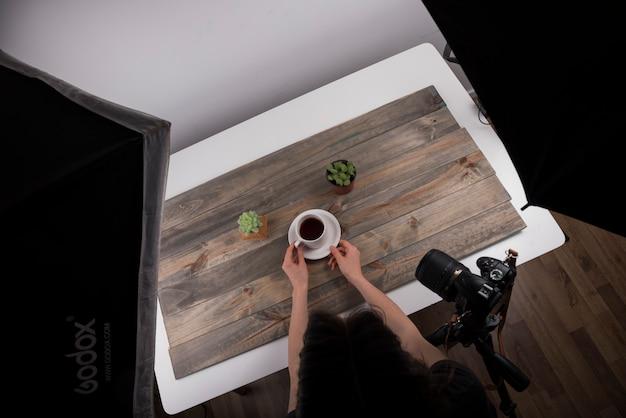 スタジオで撮影するためのお茶のカップを配置する写真家の立面図