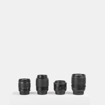 白い背景の前のテーブルに配置された様々なカメラレンズ