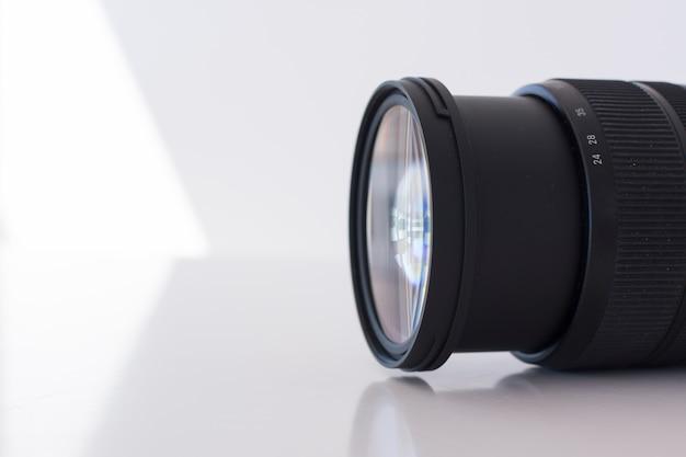 白い背景の上の現代のデジタルカメラのレンズのマクロ撮影