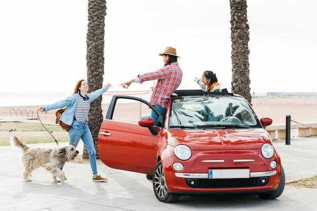 Пара в машине приветствие женщина с собакой на открытом воздухе