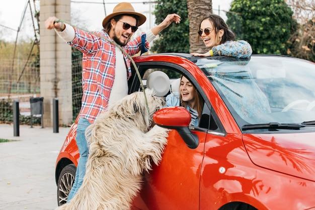 Люди стоят с большой собакой возле машины