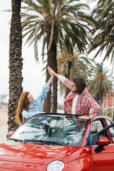 若い陽気な女と男の車からハイファイブを与える