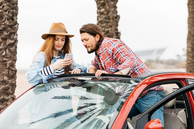 車から傾いている男の近くのスマートフォンを持つ若い陽気な女性