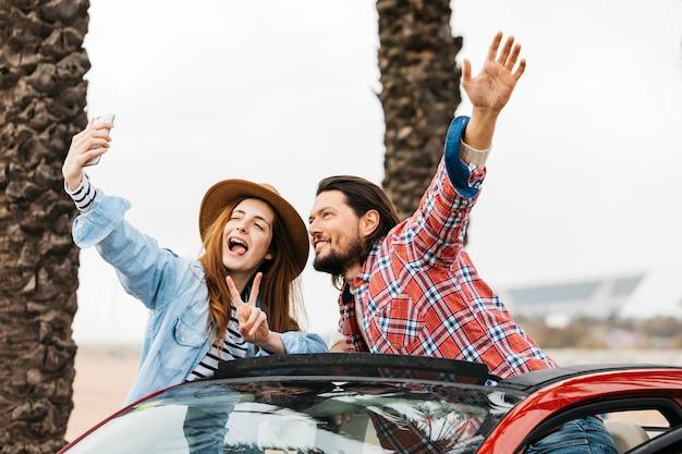 Молодая жизнерадостная женщина и мужчина, высовывающиеся из автомобиля и делающие селфи на смартфоне