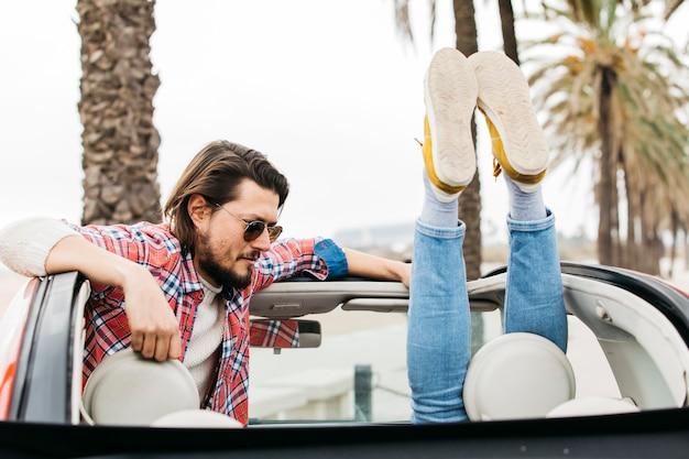 車から傾いている女性の足の近くの若い男