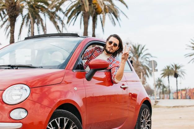 男は車から傾いていると平和のジェスチャーを示す