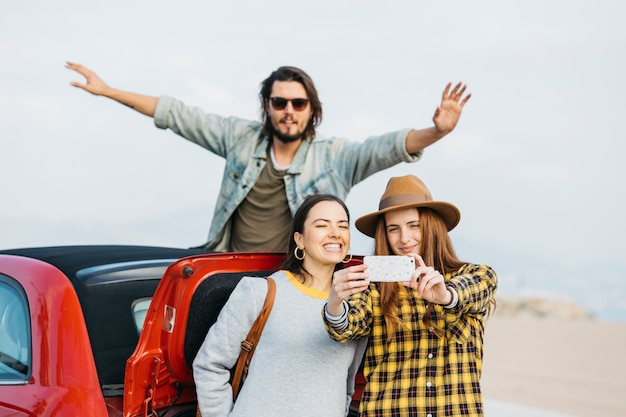 Женщины, принимающие селфи на смартфоне возле багажника и человек, высовывающийся из авто