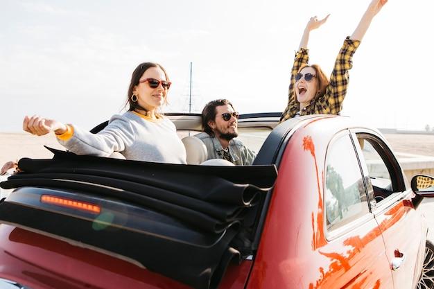 自動車から身を乗り出して手を上げたと笑顔の女性の近くの車に座っている正男