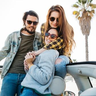 Мужчина и улыбающиеся женщины обнимаются и высовываются из авто