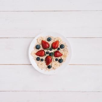 テーブルの上にボウルにさまざまな果実とオートミール