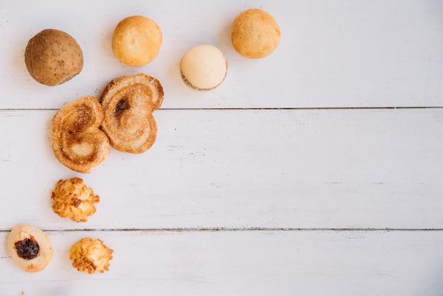 Разные печенья разбросаны по деревянному столу