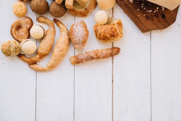 Различные хлебобулочные изделия разбросаны по светлому деревянному столу