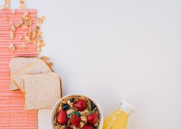 トーストの近くの果実とコーンフレーク