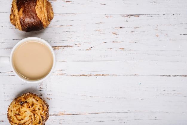 木製のテーブルの上の甘いパンとコーヒーカップ