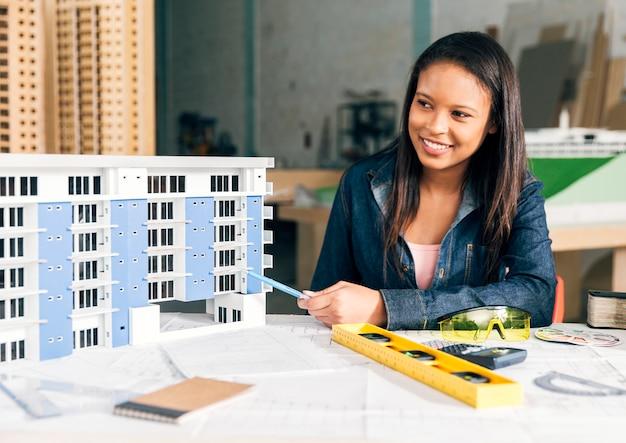 建物のモデルを示すアフリカ系アメリカ人女性の笑みを浮かべてください。